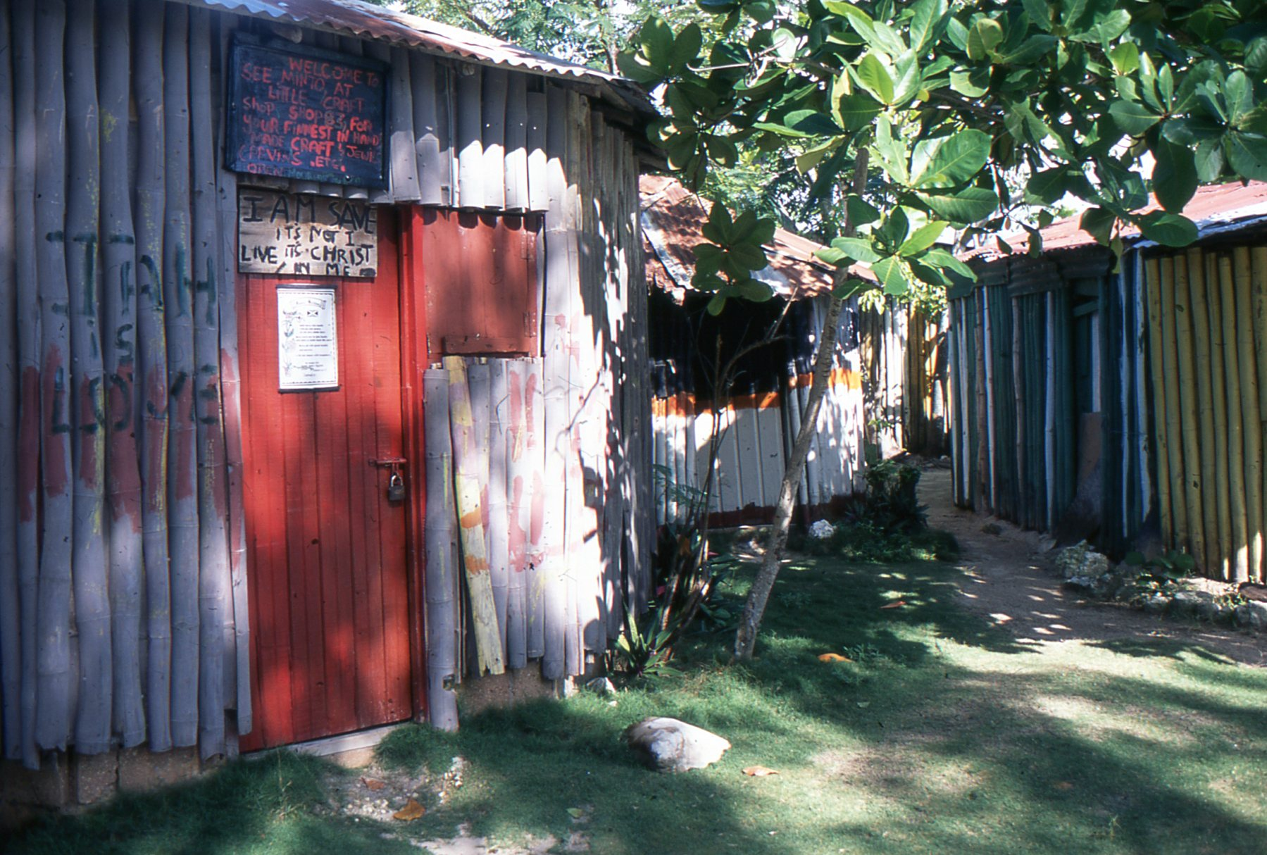 """Along Jamaica's North Coast, near Cooper's Pen, this stall holder proclaims """"It is not I live, it is Christ by me,"""" as well as """"Jah is love."""""""