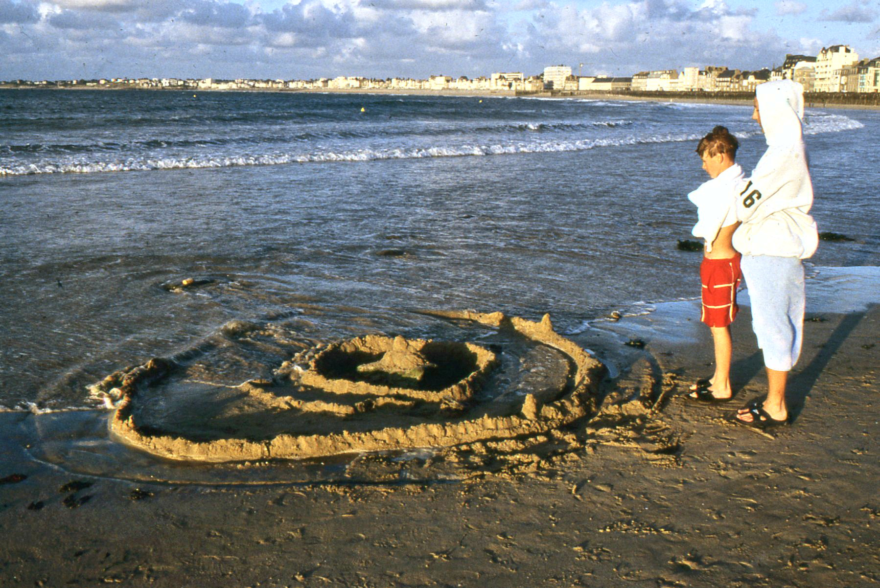 Evan and Alex Gabriel witness the final moments of their sand castle.