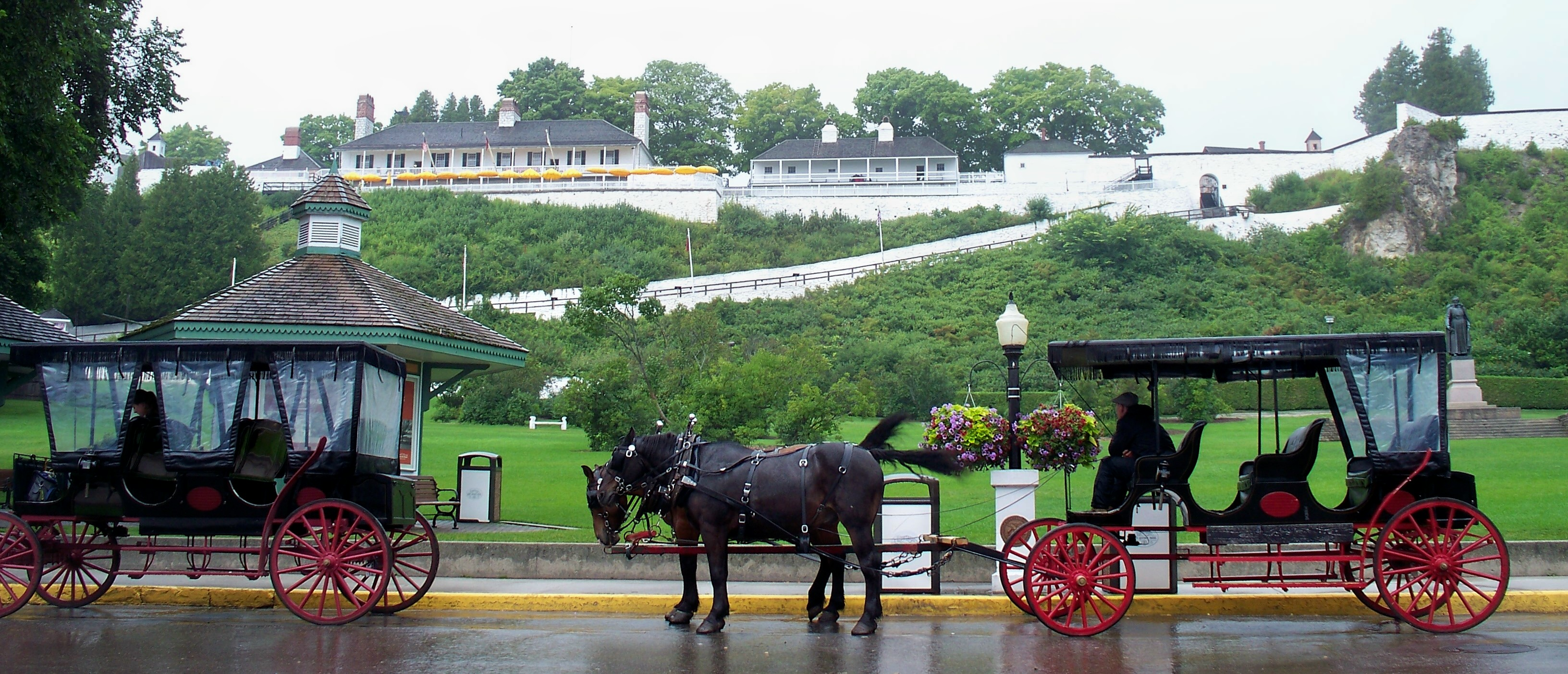 Horse carriages wait out the rain beneath the spreading bulk of Fort Mackinac.