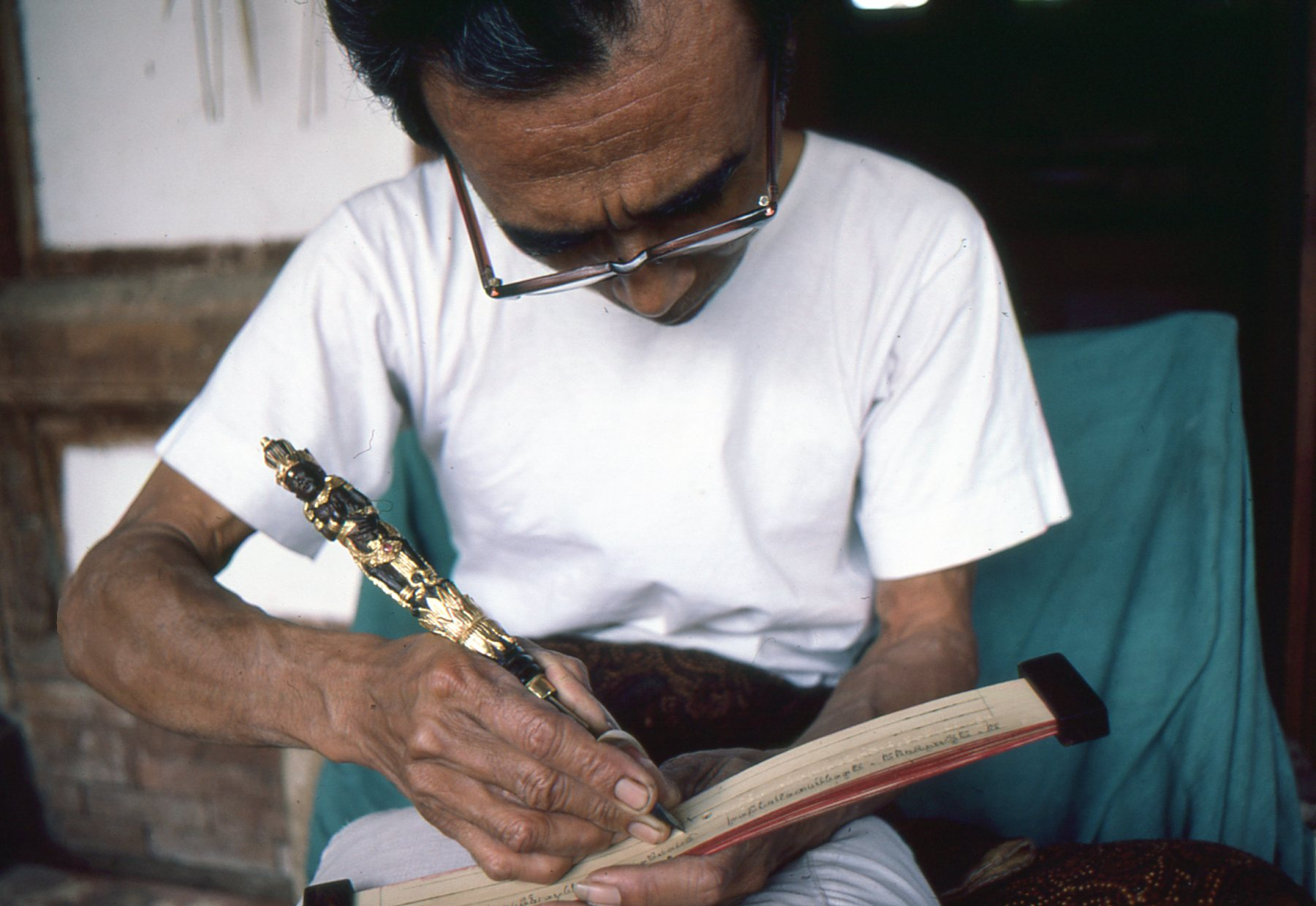 In Tenganan, the best-preserved Bali Aga village, a scribe writes the ancient lontar script in a traditional book of banana leaves.